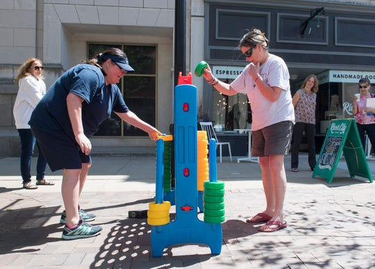Dee Ozechowski, left, and her mother Cathy Rohner, right, play a game of life-size Connect Four on Main Street while people stop and watch Monday, April 22, 2019.