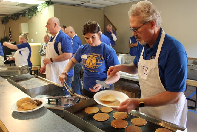 Brad Culbert dishes out pancakes, while Kelby Bickley readies sausages for a plate at the annual Kiwanis Pancake Festival.