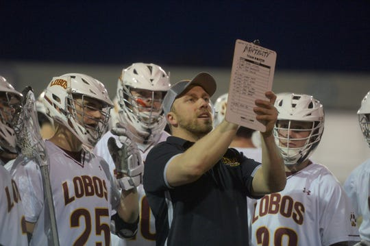 Rocky Mountain High School's boys lacrosse team, which draws players from throughout Poudre School District, looks on as assistant coach John Belleau draws up a play during a timeout in an April 23, 2019, win over Erie at French Field. Rocky Mountain lost 7-6 to Rock Canyon on Wednesday night in the first round of the Class 5A state playoffs.