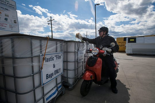 Dave Fritz drives up on his Honda scooter to drop off a few plastic bags into a bin for plastic bags and film on Wednesday, April 24, 2019, at the Timberline Recycling Center in Fort Collins, Colo.