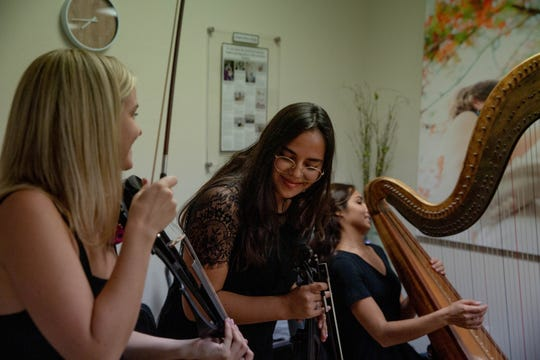 Jade Gibson, center, takes a bow with band mates Sarah Ball and Sapphire Gibson after the three performed together at the Neubek Photographers studio in Naples on Friday, April 19, 2019. Jade Gibson, a student at Florida Gulf Coast University, is part of an entrepreneurship program at the university.