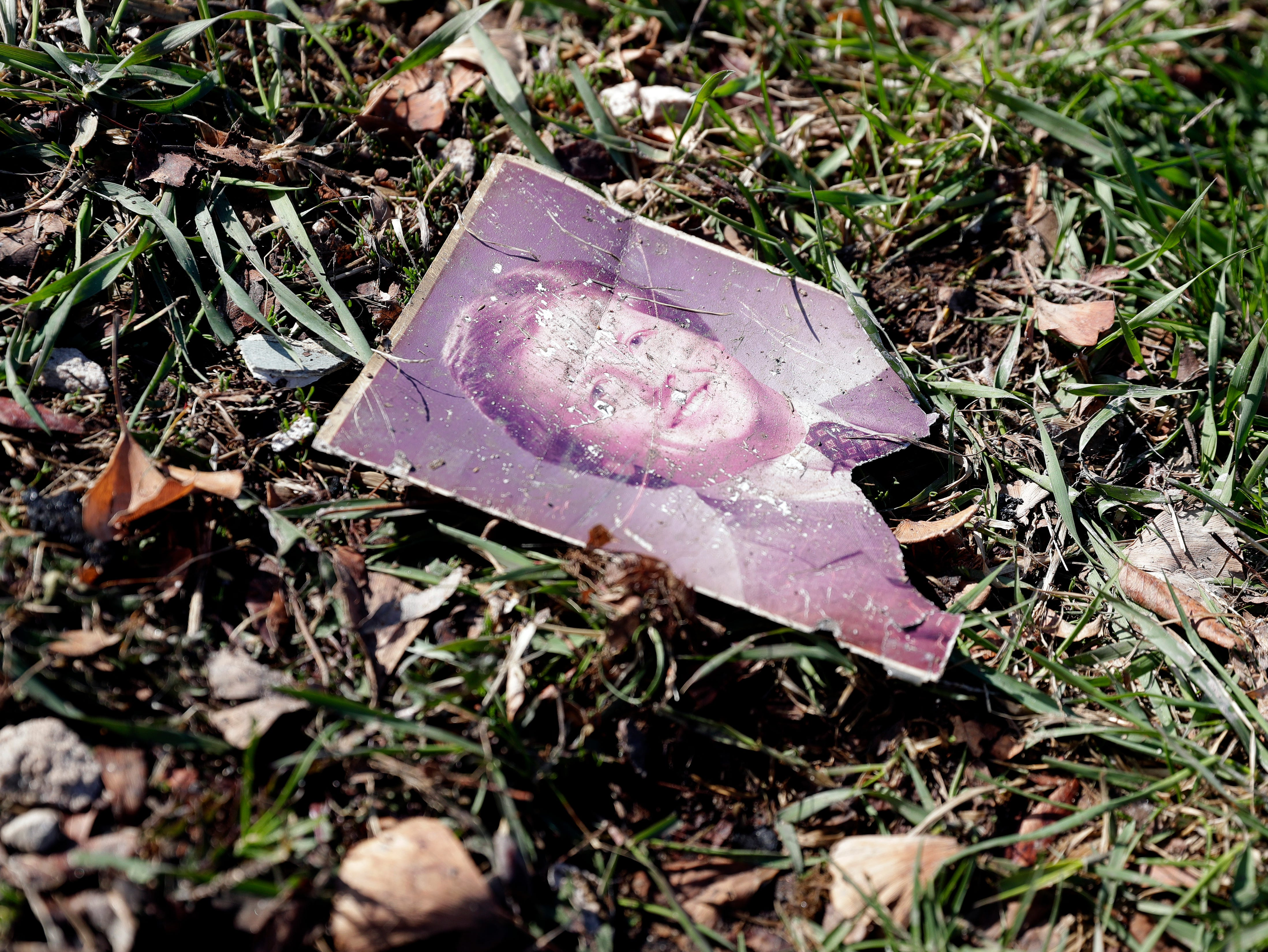A photograph lies in the grass near the remains of 100 S. Broadway in De Pere on April 24, 2019, after the building burned down overnight. The building was home to Ogan Restaurant, apartments and a number of other businesses.