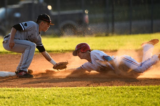 J.L. Mann's Brady Wharton (14) slides towards third base as Boiling Springs' David Starnes (2) attempts to get him out during their playoffs game Tuesday, April 23, 2019.