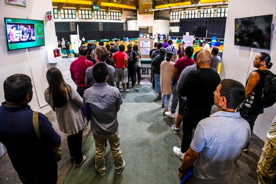 Job seekers sign in during the opening of the University of Guam Job Fair, hosted by University of Guam's Career Development Office, at the Calvo Field House in Mangilao April 24.