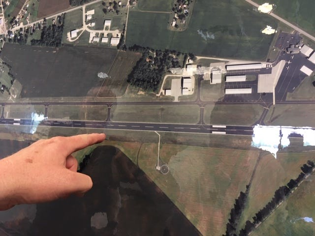Henderson County Coroner Bruce Farmer points out on an aerial photograph where the plane crashed at the Henderson City-County Airport.