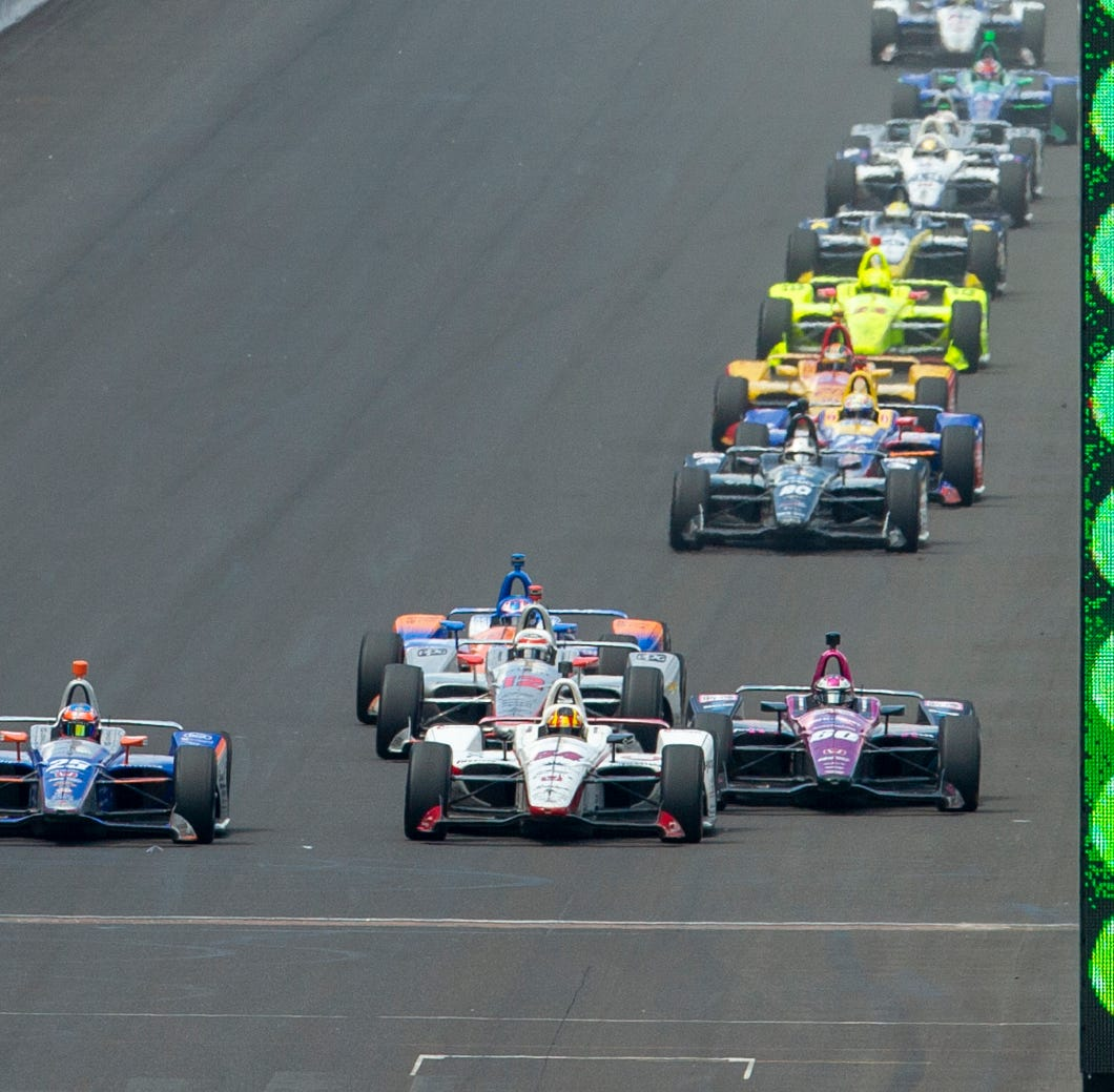 Andretti Autosport IndyCar driver Stefan Wilson (25), left, looks for a line into the first turn as the field takes the Green Flag for the final restart of the race at Indianapolis Motor Speedway on Sunday, May 27, 2018. Team Penske IndyCar driver Will Power (12) won the 102nd running of the Indianapolis 500.