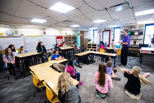 """Kirk Ryan, a fifth-grade teacher, talks with students in a """"healthy life stars"""" group during a Lucas on Campus (LOC) after school program, Tuesday, April 23, 2019, at Robert Lucas Elementary in Iowa City, Iowa."""