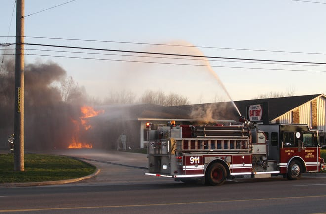 Water is pumped to the roof of Complete Battery Source in Genoa Twp. Tuesday, April 23, 2019 to put out a fire that is thought to have started on the roof.