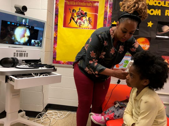 Engelhard Elementary school nurse Nicole Lasley examines Heaven Coleman, a second-grader, while a nurse practitioner from Norton Healthcare watches remotely. April 24, 2019