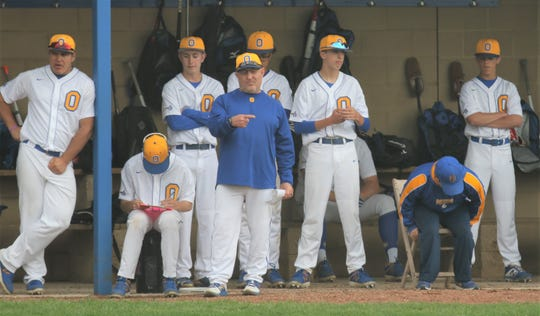 Ontario pitching coach Mike Ellis relays a sign to his catcher during the Warriors 6-2 win over Clear Fork on Tuesday. Noah Creed credited Ellis for his 1-hitter.