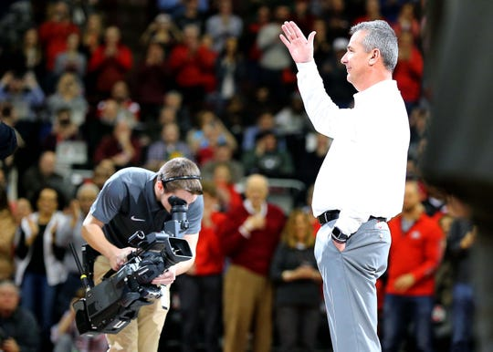 Retired Ohio State football coach Urban Meyer waves to the crowd during a basketball game against Michigan State this year inside Value City Arena.