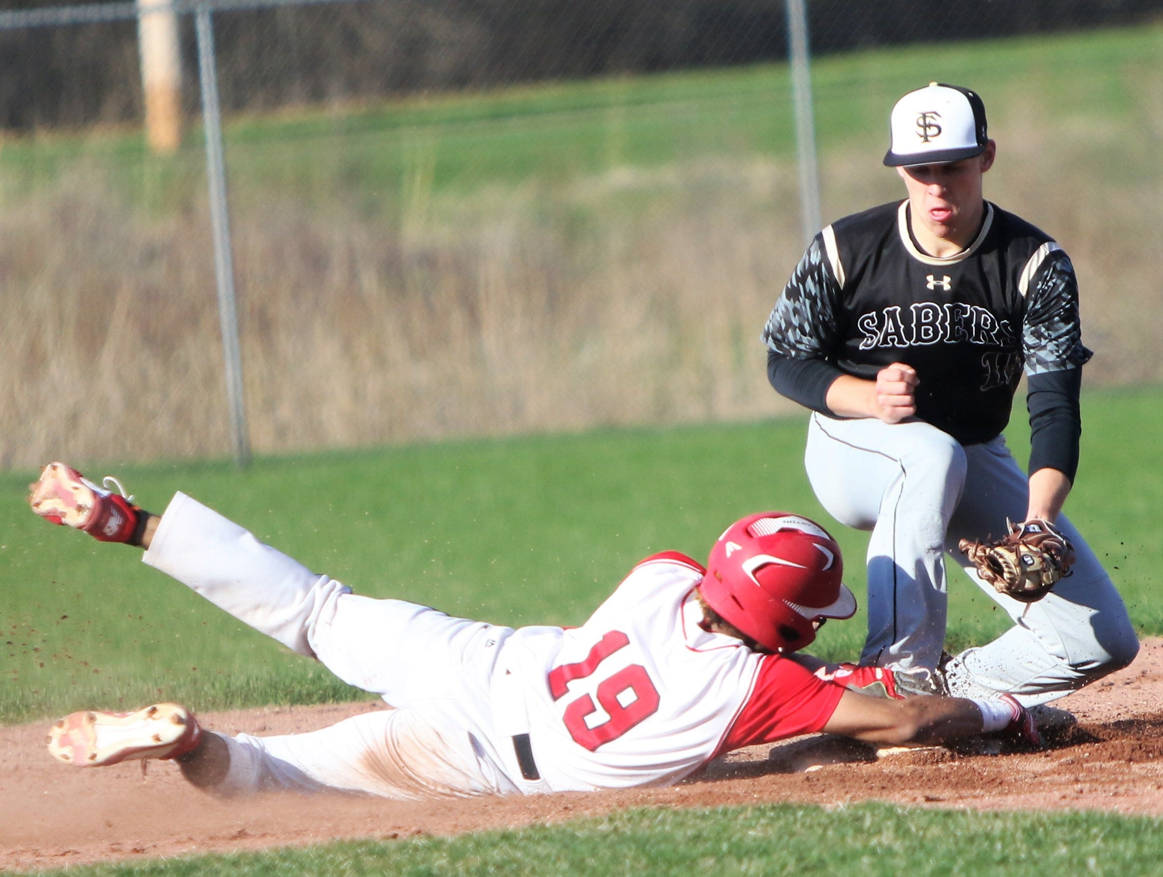 South Milwaukee freshman Carmelo Ortiz (19) hangs onto second base while sliding in safely with a double against Franklin on April 23, 2019.