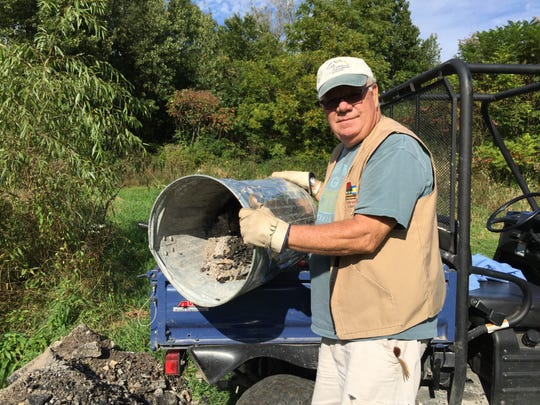 Bob Heft empties a garbage can filled with ash while volunteering as a campground host at Wylausing State Park.
