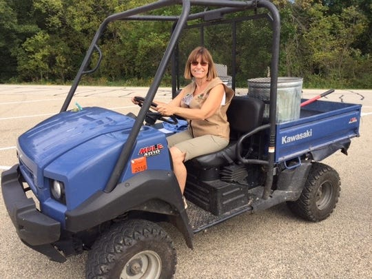 Kathy Lenz drives an all-terrain vehicle while volunteering as a campground host at Wyalusing State Park in Bagley.