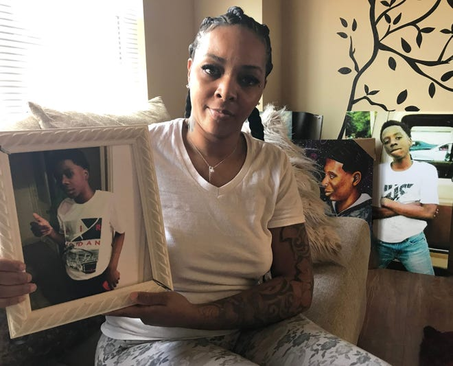 Dombanee Lincoln holds a photo of her son, Dennis King, who was murdered a year ago in Milwaukee. Other tribute photos are on display in her living room.