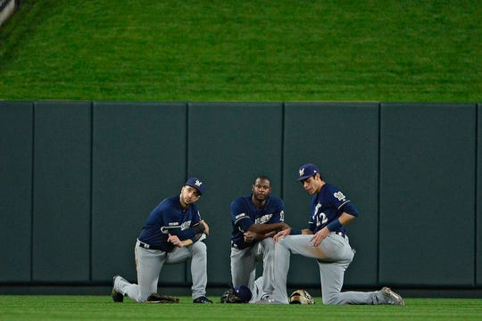 The Brewers' Ryan Braun, Lorenzo Cain and Christian Yelich (from left) take a knee during a pitching change.