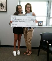 Mountain Home high-school student Emili Elkins (eft) presents Michelle Padgett with a $1,000 donation to the Hayden Padgett Safe In His Arms Foundation on Tuesday.