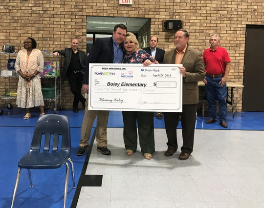 Media Ministries General Manager Bryan Cordill presents a check for $35,350 to Boley Elementary Principal Sandy Bates and Ouachita Parish Schools Superintendent Don Coker on Wednesday at George Welch Elementary in West Monroe.