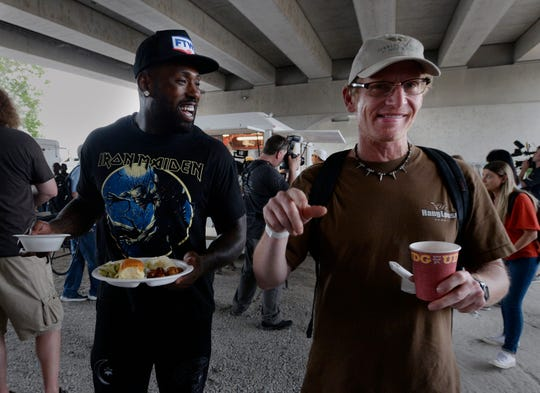 Tennessee Titans tight end Delanie Walker, left, carries a meal for Mark McCormick under the Jefferson Street bridge Tuesday, April 23, 2019, in Nashville. The Titans joined with the Bridge Ministry and other volunteers to help feed the homeless in Nashville.