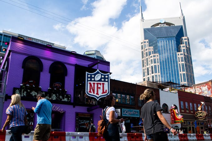 People walk along Broadway before the NFL Draft Wednesday, April 24, 2019, in Nashville, Tenn.