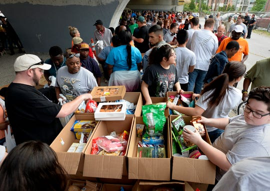 Volunteers hand out food to the homeless under the Jefferson Street bridge on Tuesday, April 23, 2019, in Nashville, Tenn. The Titans joined with Bridge Ministry and other volunteers to help the homeless in Nashville.
