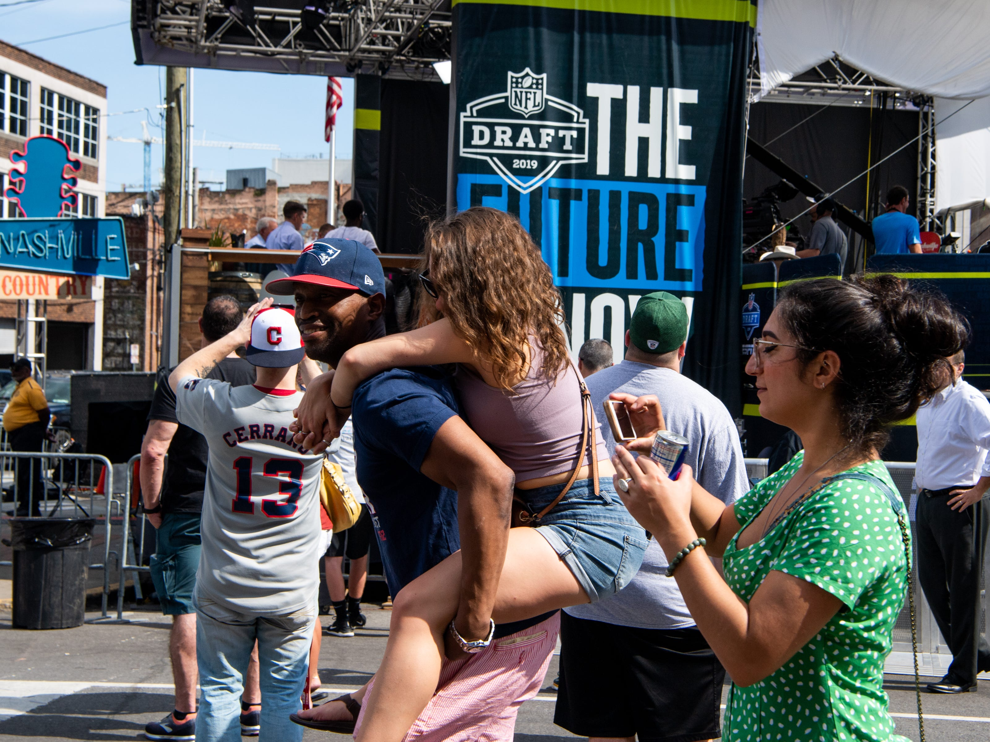 People walk and are carried along Broadway before the NFL Draft Wednesday, April 24, 2019, in Nashville, Tenn.