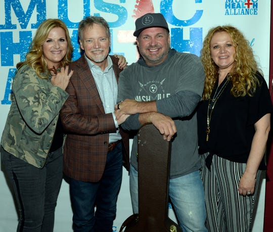 "Trisha Yearwood and Garth Brooks were surprise guests at the benefit concert ""We All Come Together"" for John Berry and Music Health Alliance Tuesday night. From left: Trisha Yearwood, John Berry, Garth Brooks, Robin Berry."