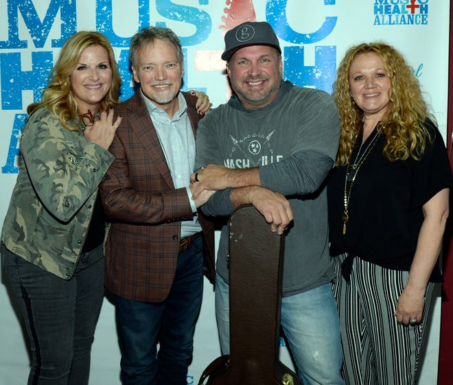 """Trisha Yearwood and Garth Brooks were surprise guests at the benefit concert """"We All Come Together"""" for John Berry and Music Health Alliance Tuesday night. From left: Trisha Yearwood, John Berry, Garth Brooks, Robin Berry."""