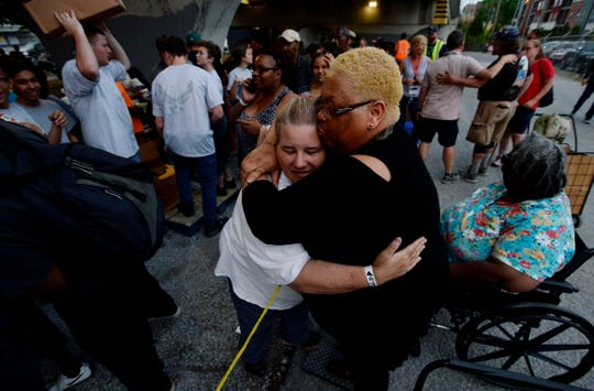 Hope Page gets a hug from Cleo King while getting bags of food from volunteers under the Jefferson Street bridge Tuesday, April 23, 2019, in Nashville. The Titans joined with the Bridge Ministry and other volunteers to help the homeless in Nashville.