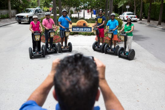 Dominick Dimolfetta, a tour guide with Segway Tours of Naples, takes a photo of the Patel family, tourists from Ocala, Fla., during a stop at the Naples Pier in August 2016. Hoteliers and tourism experts expect a good Memorial Day weekend in Florida and are hopeful about the summer.