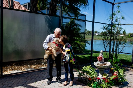 """Jim and Linda Hansen kiss their dog, Lizzie, at their home in Naples Lakes Country Club on Tuesday, April 23, 2019. The Hansens received Lizzie through the """"Lucky Dog"""" TV series, which trains shelter dogs and finds them homes with families across the United States."""