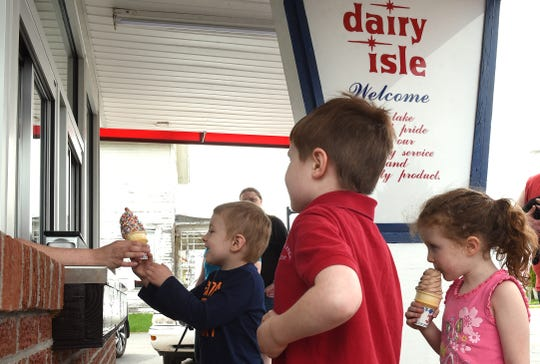 Toby Bowman, 5, gets his chocolate sprinkle cone as Robert Pawley, 6, waits for his order, and Madison Pawley, 4, digs into her chocolate cone Wednesday at the Dairy Isle on East Main Street. The ice cream and snack shop, has reopened following an 11-month closure after a vehicle crashed into the building.