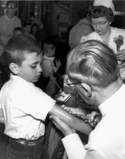 Dr. F. E. Keeling gives second-grader Ron Cole a shot of the Salk vaccine in April 1955. More than 300 first- and second- graders were inoculated per hour that day in a community-wide effort to administer the vaccine that conquered polio. Jay County was the scene of one of the worst polio epidemics in history, in 1949, leading the state with the number of cases that summer.