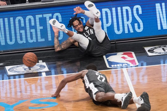 Brooklyn Nets guard D'Angelo Russell, top, and guard Caris LeVert (22) fall on the court during the second half of Game 4 of a first-round NBA basketball playoff series against the Philadelphia 76ers, Saturday, April 20, 2019, in New York.