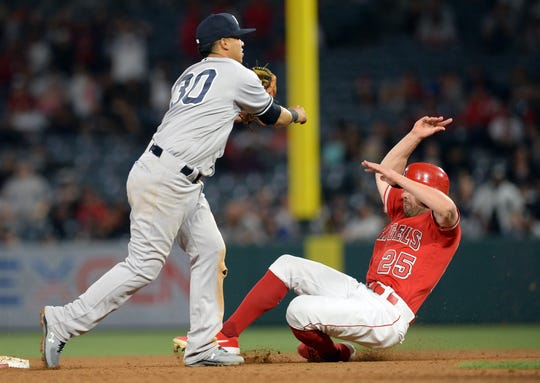 Los Angeles Angels center fielder Peter Bourjos (25) is out at second on a double play as New York Yankees second baseman Thairo Estrada (30) throws to first for the out against catcher Kevan Smith (44) during the eighth inning at Angel Stadium of Anaheim on Tuesday, April 23, 2019