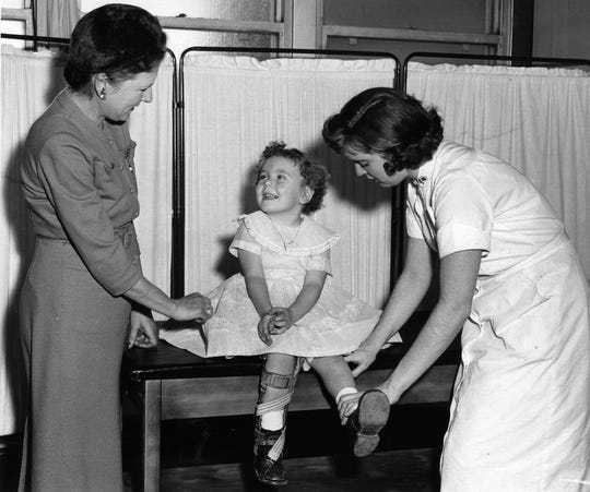 Former poster polio girl, three-year-old Eileen Connor of Waldwick, thoroughly enjoys her current therapy treatments at Bergen Pines as administered by nurse Brenda Bellaviana while Northern District Campaign Chairman Desiree Mittelstadet of Ridgewood looks on. JAN 14 1958
