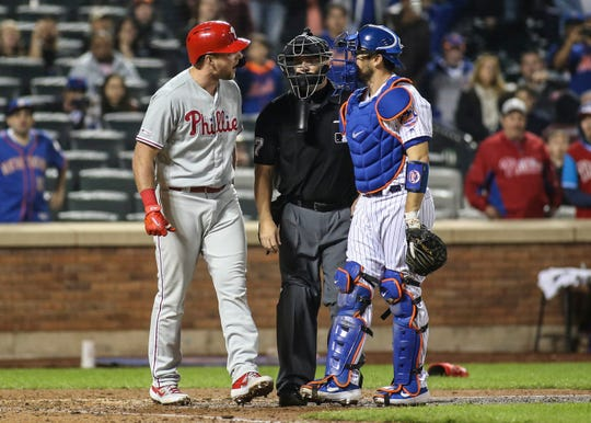Apr 23, 2019; New York City, NY, USA; Philadelphia Phillies first baseman Rhys Hoskins (17) exchanges words with New York Mets catcher Travis d'Arnaud (18) after almost getting hit by a pitch in the ninth inning at Citi Field.