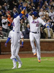 New York Mets' Todd Frazier (21) celebrates with teammate Robinson Cano (24) after hitting a grand slam home run during the fifth inning of a baseball game against the Philadelphia Phillies Tuesday, April 23, 2019, in New York. (AP Photo/Frank Franklin II)