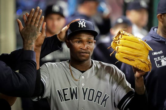 New York Yankees starting pitcher Domingo German celebrates in the dugout after leaving the game against the Los Angeles Angels during the seventh inning of a baseball game in Anaheim, Calif., Tuesday, April 23, 2019.