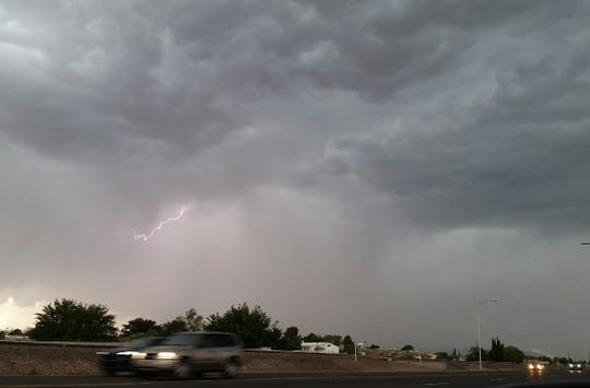 As viewed from South Main Street, a streak of lightning flashes in the middle of a rain and hail storm the evening of Tuesday, April 23, 2019 in Las Cruces.