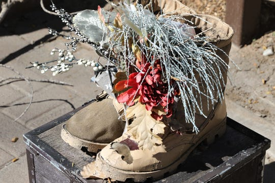 A pair of empty soldier's boots and flowers are seen Wednesday in All Veterans Memorial Plaza in Farmington.