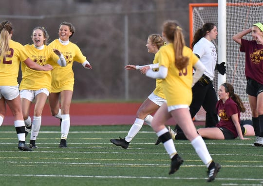 South Lyon Lions begin to converge on Lexi Nabozny, second from left, after she scores the game-winning goal on April 23 against Milford.