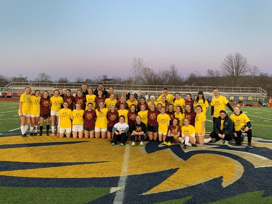 The South Lyon and Milford girls soccer teams pose together after their game which raised money for Mott Children's Hospital.