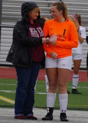 South Lyon East's Rachel Craig, girls soccer booster VP, presents a $100 check on behalf of the South Lyon East girls soccer team to South Lyon senior captain Carmen Sweigard for their upcoming Gold Out to support Mott's Children's Hospital.