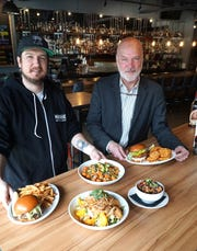 The Morrie's chef Derik Watson, left, and the restaurant's Director of Operations Keith Schofield, proudly display some of the Royal Oak restaurant's fare - including the very popular KungPo cauliflower appetizer - at lower right.