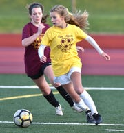 Regan Dancer, right, tries to turn towards the Milford goal.