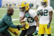 Packers running back Aaron Jones (33) performs a team drill with assistant Ben Sirmans last April.