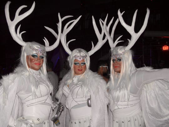 Three White Party attendees dress in white in April 2016 at the Palm Springs Convention Center.