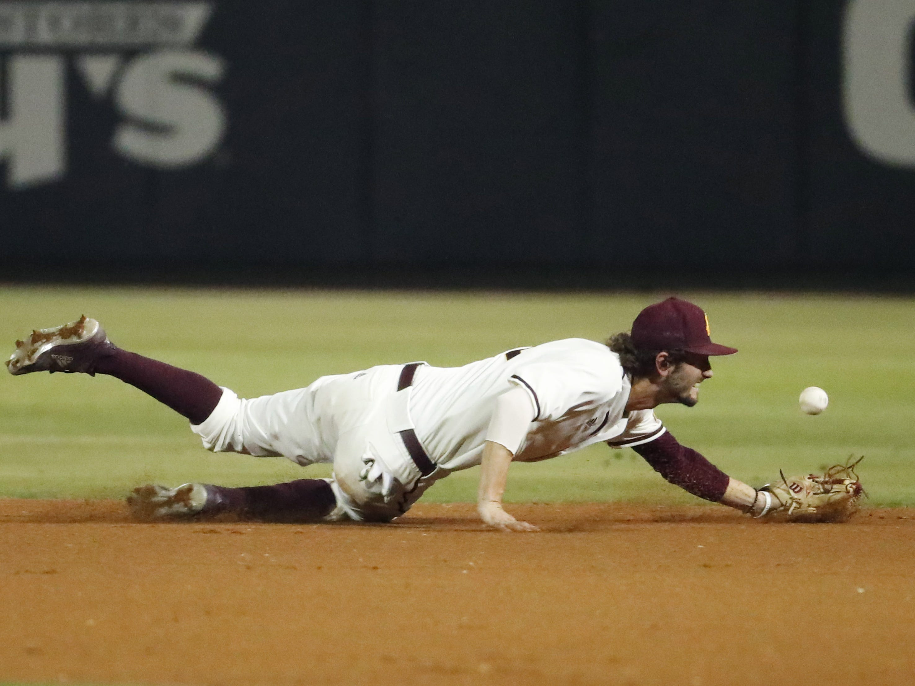 A ground ball gets by ASU second baseman Drew Swift during the fifth inning against UNLV in Phoenix April 23, 2019.