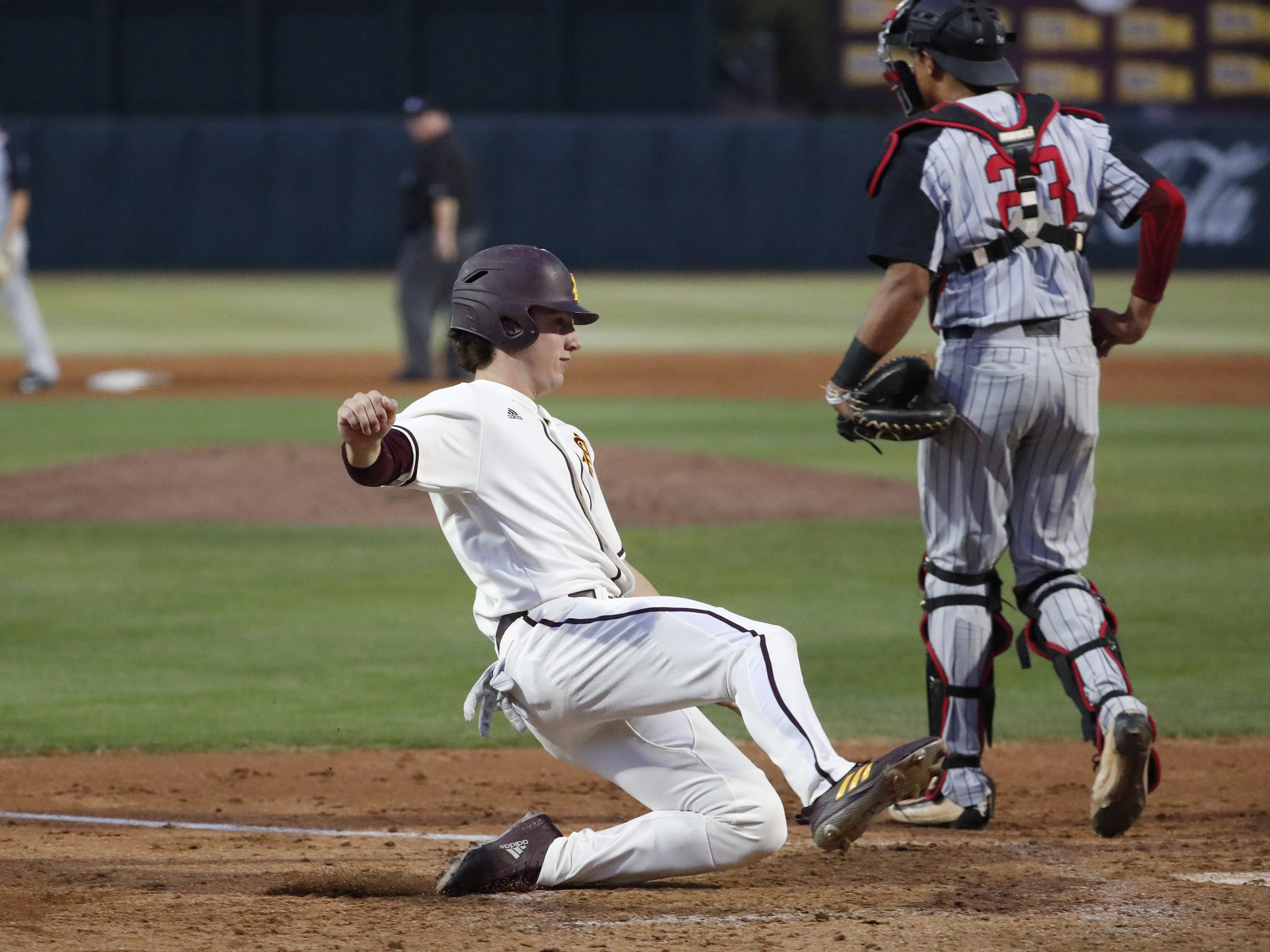 ASU's Trevor Hauver scores behind UNLV catcher Jacob Godman during the second inning in Phoenix April 23, 2019.